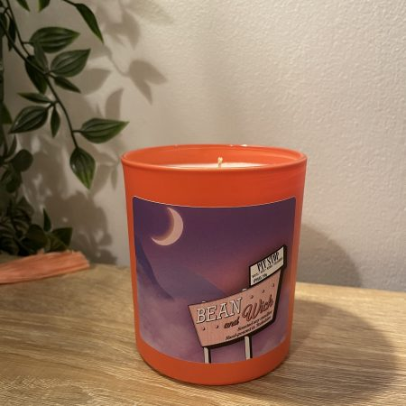 Beanandwick candle. Coral jar with a purple Label. On the label is a Beanandwick motel sign with a purple dreamy backdrop of mountains and a crescent moon.