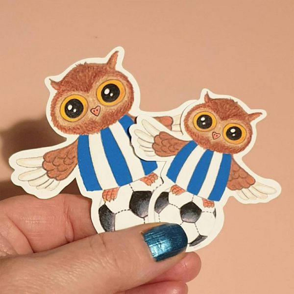 a cute little owl in a blue and white Sheffield Wednesday shirt resting on a black and white football sticker with a larger sticker behind being held in a hand